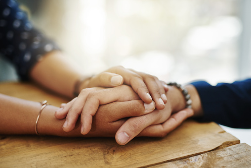 A woman's hands holding a man's hand to offer comfort